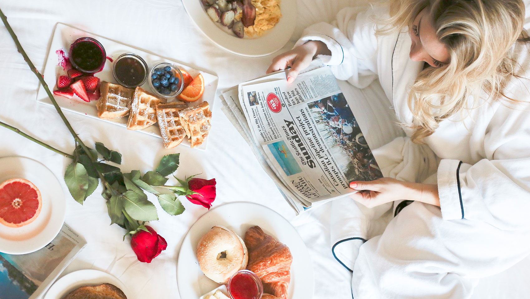 Breakfast spread on bed with roses, newspaper and blonde woman in white robe
